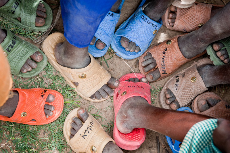 We distribute shoes to the children to stop the passing of parasites